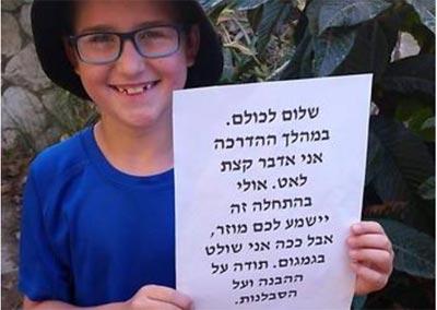 אורי פישר מחזיק שלט לבני כיתתו