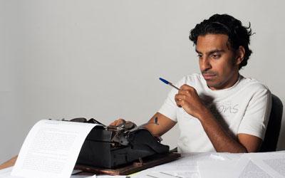 אמיר ראג'פורקר יושב מול מכונת כתיבה