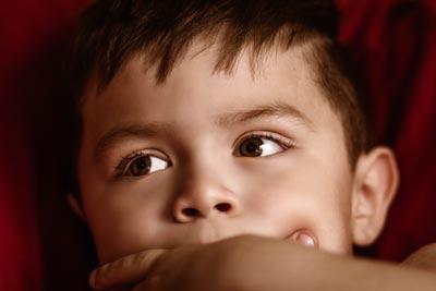 ילד מניח יד על פיו